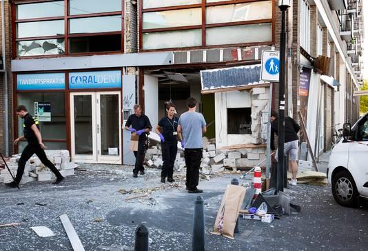 Politiemensen doen onderzoek bij de opgeblazen pinautomaat op het Smaragdplein. De gevel ligt eruit en de omgeving is bezaaid met glas.