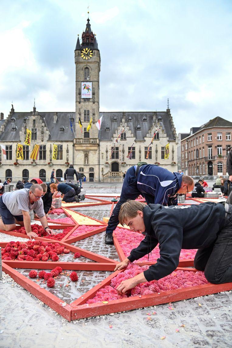 Tientallen vrijwilligers hielpen mee aan het leggen van het bloementapijt.