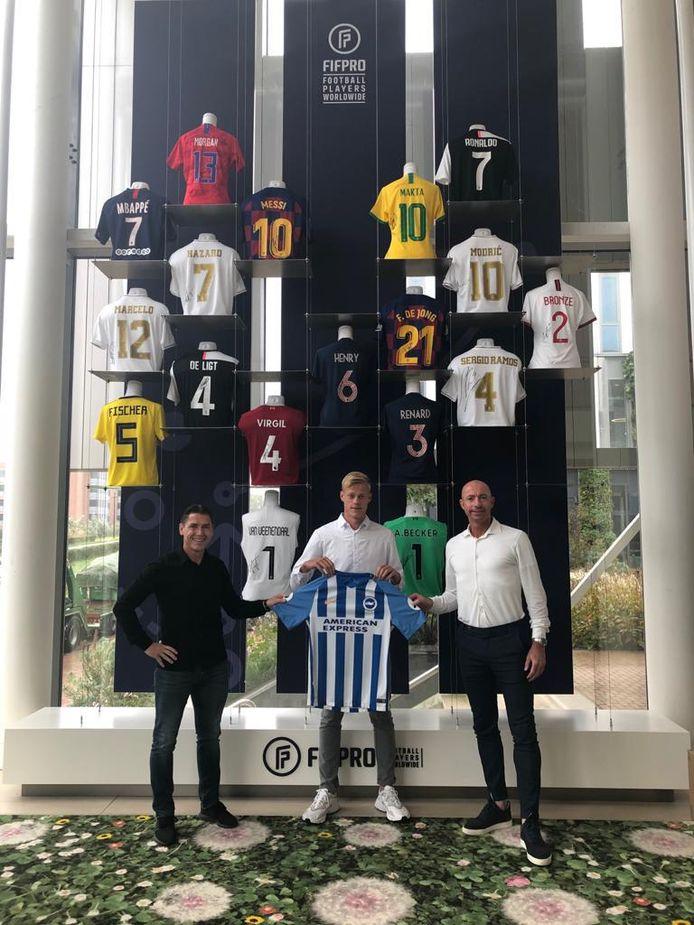 Jan Paul van Hecke, met het shirt van zijn nieuwe club Brighton & Hove Albion, samen met zaakwaarnemers Louis Laros (links) en Patrick van Diemen.