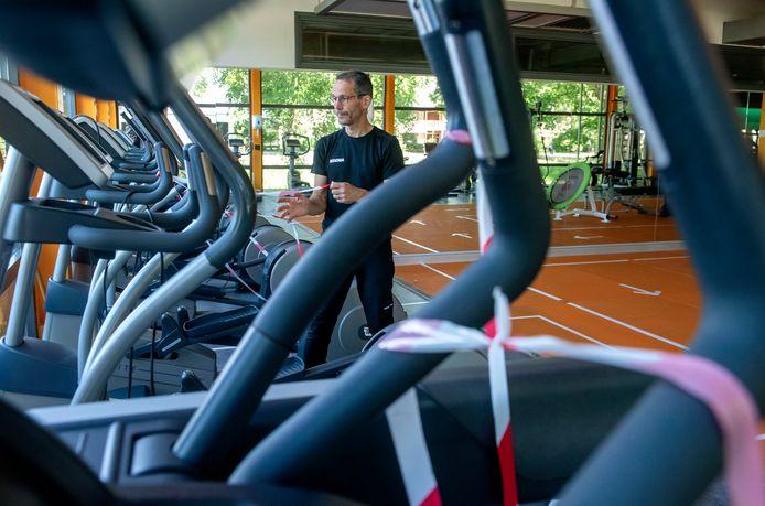 Om de sporters uit elkaars buurt te houden zijn op de vloer pijlen en vakken aangegeven. Sjaak Salomé doet linten om de apparaten die niet worden gebruikt.