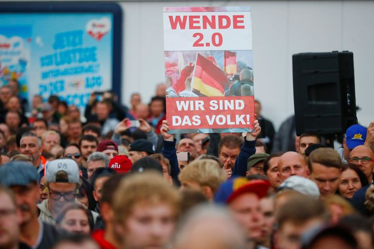 Demonstranten houden een bord omhoog met daarop de boodschap 'Wij zijn het volk''. Beeld REUTERS