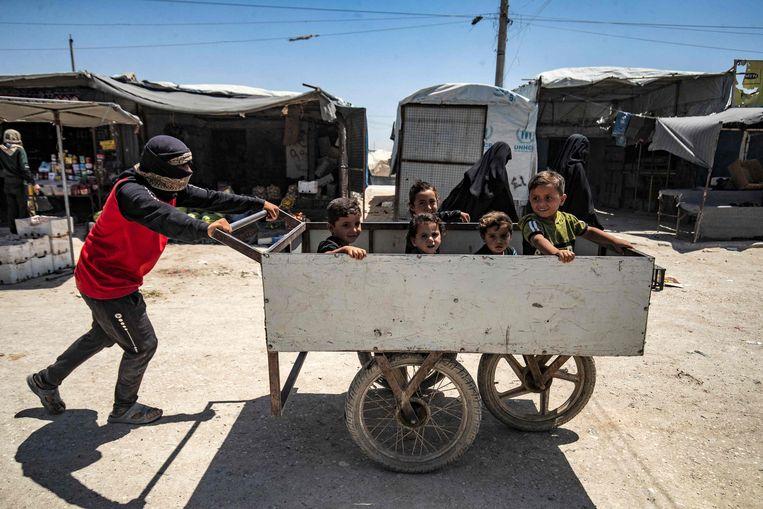 Een man duwt een kar met kinderen in het Koerdische kamp al-Hol in Noordoost-Syrië, waar vermeende familieleden van IS-strijders verblijven. Beeld Delil Souleiman / AFP
