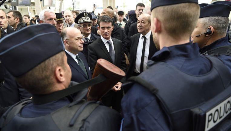 De Franse premier Valls (midden) praat met de politie in Parijs. Beeld epa