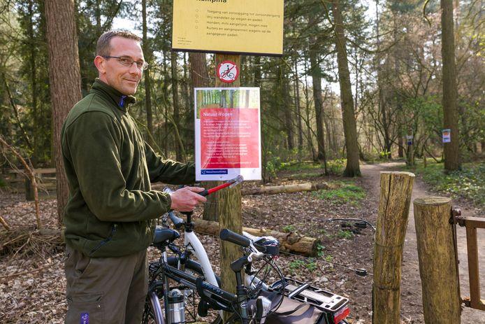 Boswachter Niels Vogels hangt een bordje op met aanvullende regels voor bezoekers van het bos.