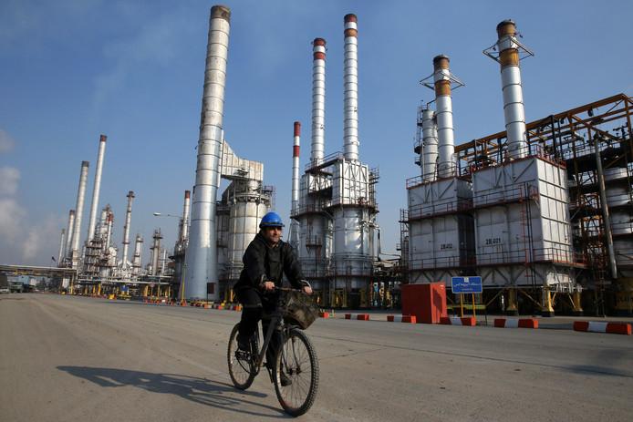 Een medewerker van de Iraanse olieraffinaderij ten zuiden van Teheran. De olieprijzen dalen mede doordat acht landen olie mogen blijven kopen van Iran.