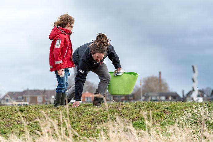Door weer en wind: Aidan Scherpbier zoekt met zoontje Skip (6) naar plastic afval langs de IJssel bij Oene.