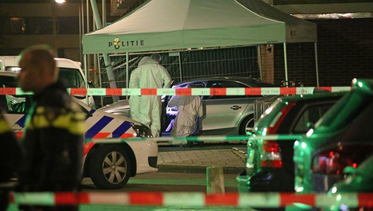 De politie doet onderzoek bij de auto waar de man is doodgeschoten. Beeld anp