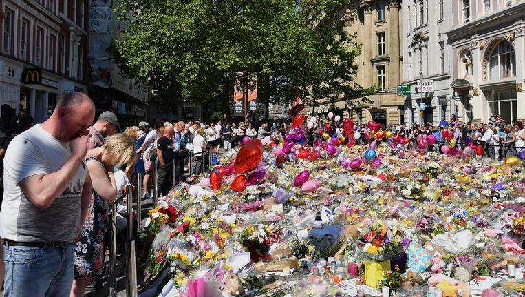 Mensen rouwen bij een bloemenzee in Manchester. Beeld Getty Images