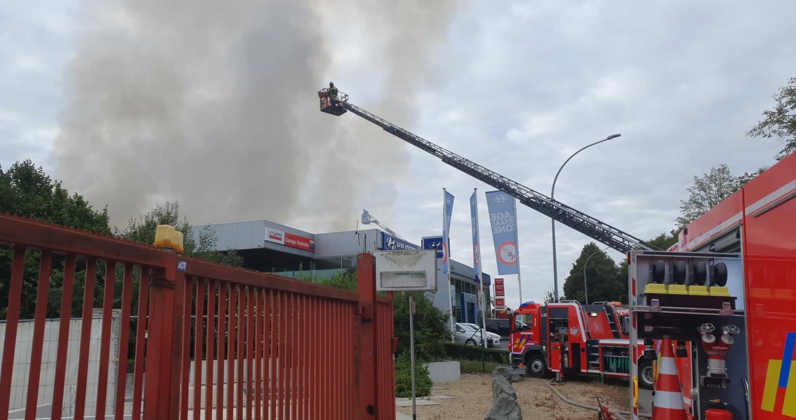 De brandweer probeert de showroom met man en macht te vrijwaren.