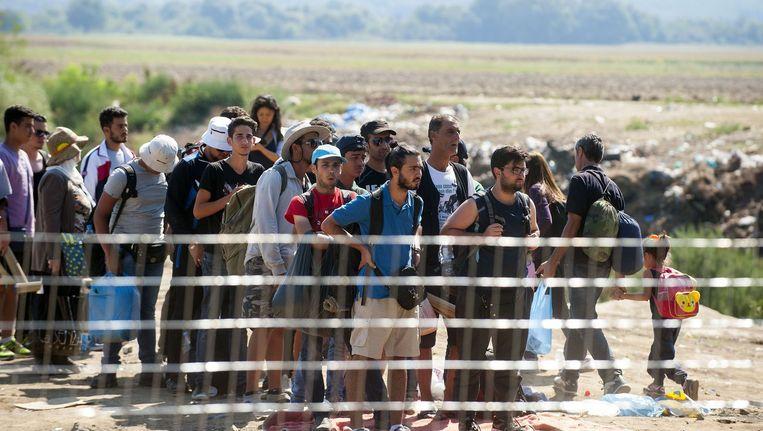 Migranten wachten aan de grens tussen Griekenland en Macedonië tot de Macedonische politie hen toelaat. Beeld afp