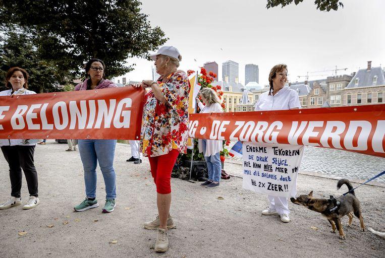 Vorige week voerden zorgverleners met een spandoek van 130 meter lang actie bij de Hofvijver voor hogere salarissen in de zorgsector. Beeld ANP