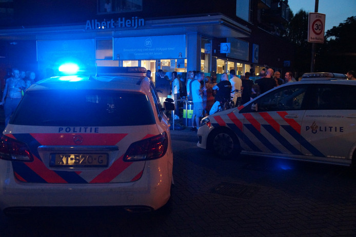 Politie en veel bezoekers voor de deur bij de Albert Heijn aan het Bloemenoordplein in Waalwijk.
