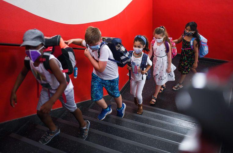 Leerlingen met mondkapjes gaan naar hun les in een basisschool in Dortmund, Duitsland. De Duitse overheid verspreidt informatie over corona niet op een hapklare manier, zoals de Nederlandse. Beeld AFP