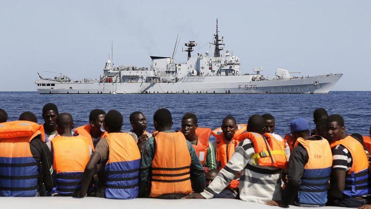 Geredde Afrikaanse migranten, met het Italiaanse marineschip Euro op de achtergrond.