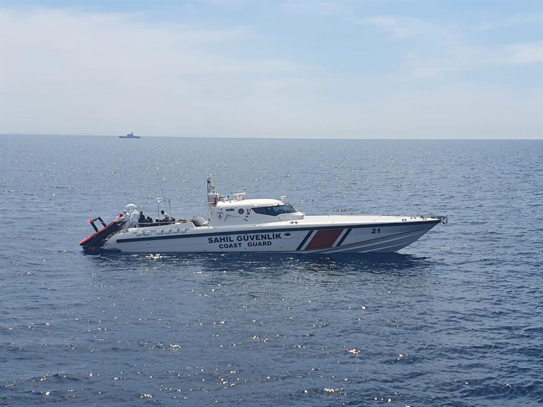 Een boot van de Turkse kustwacht, die klaarligt om de vluchtelingen zoals Jouma van het vlot te halen.