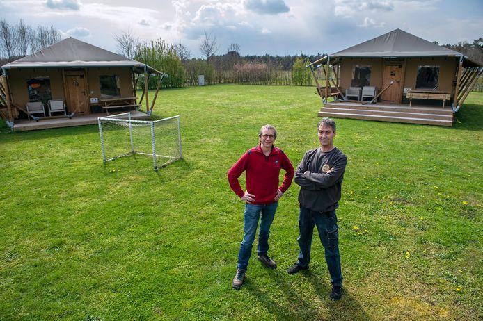 Eigenaar Ronnie Maes (rechts) en collega Hugo Roelands op 'glamping' De Bosweide in Alphen. Boven het bos achter hen steken straks grote windmolens de hoogte in, vrezen ze.