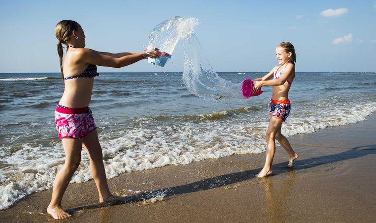 Kinderen spelen met water op het strand van Zandvoort.  Beeld ANP