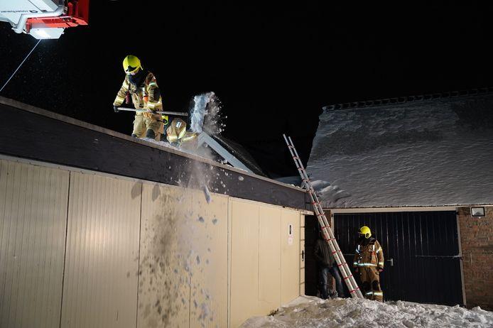 De brandweer maakte het dak van de schuur sneeuwvrij.