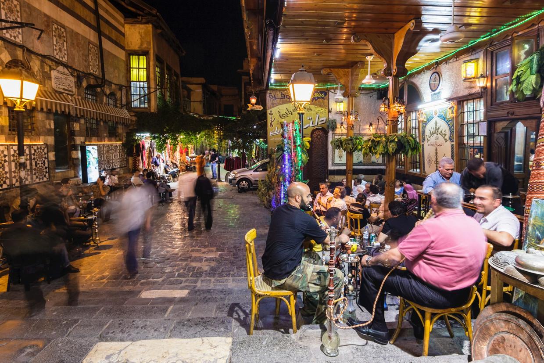 Enkele mannen roken een waterpijp in een koffiehuis in Damascus.  Beeld © Luis Fernando Dafos