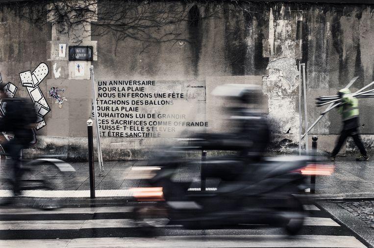 Een herdenkingsboodschap op een muur tegenover restaurant Le Petit Cambodge. 'Laten we er een feest van maken.' Beeld Karoly Effenberger