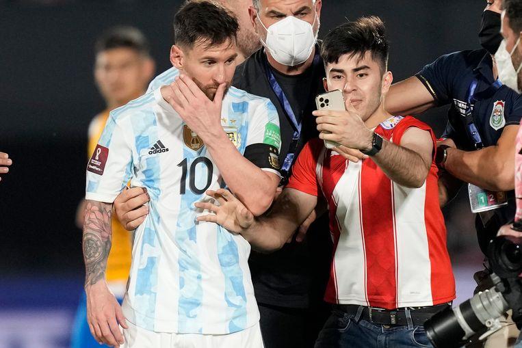 Een fan van Paraguay rende na afloop van het WK-kwalificatieduel tussen Paraguay en Argentinië (0-0) het veld op om een selfie te maken met Lionel Messi. Beeld AP