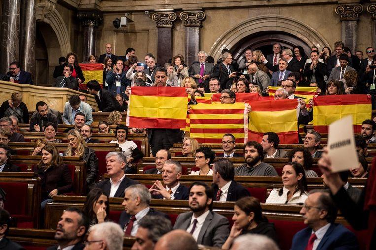 Leden van het deelstaatparlement in Barcelona tonen Spaanse en Catalaanse vlaggen na de goedkeuring van een resolutie op weg naar onafhankelijkheid. Beeld GETTY