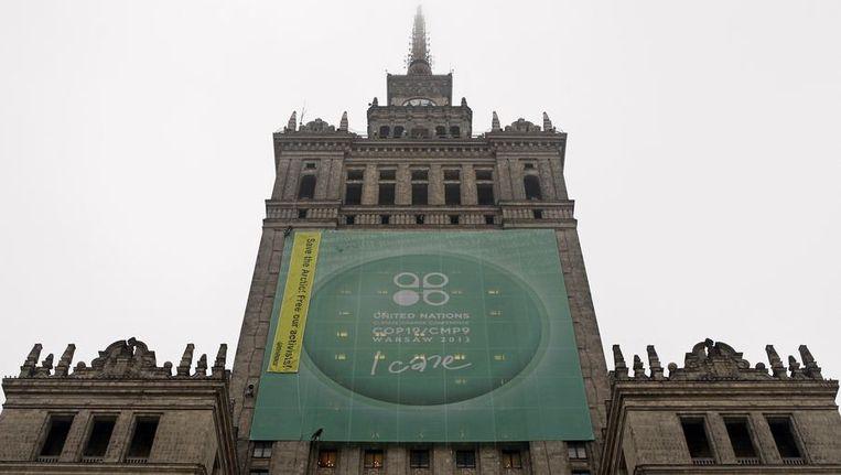 Greenpeace activisten hangen een spandoek op bij het gebouw van de Klimaattop in Warschau. Beeld reuters