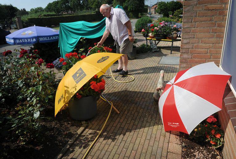 Een man besproeit zijn planten. Als het aan Vitens ligt doet hij dat met regenwater. Beeld Marcel van den Bergh