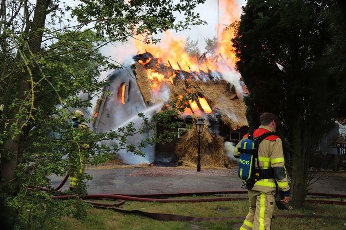 De rietgedekte boerderij staat volledig in vuur en vlam.