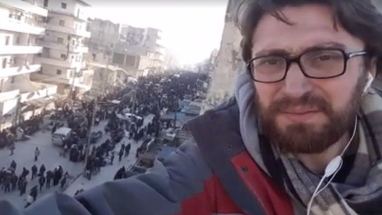 Salah al-Ashkar staat op het dak van een woning in Oost-Aleppo. Op de achtergrond inwoners die wachten op vertrek uit de belegerde enclave.   Beeld Facebook