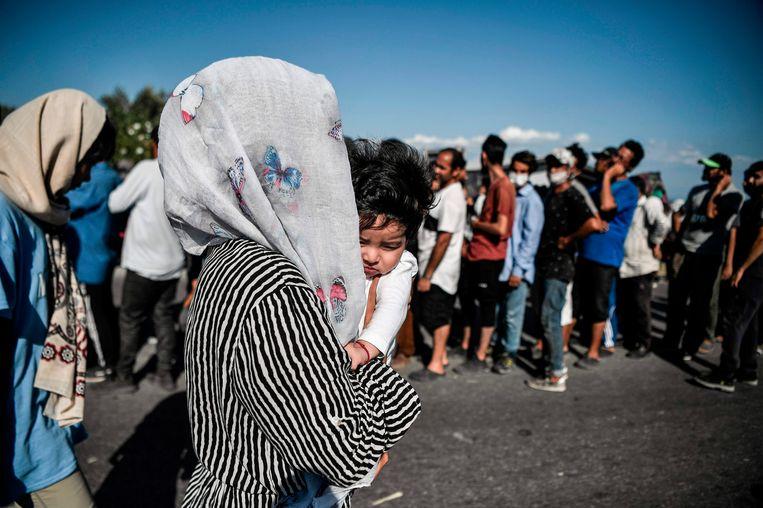 Mensen staan aan te schuiven voor voedsel na het afbranden van kamp Moria op het Griekse eiland Lesbos.  Beeld AFP