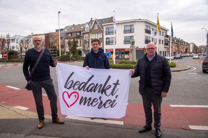 Kristof, Ignace en burgemeester Alain Pardaen hijsen de eerste de 'Bedankt-Merci-vlag' aan het Felix Beernaertsplein in Wetteren.