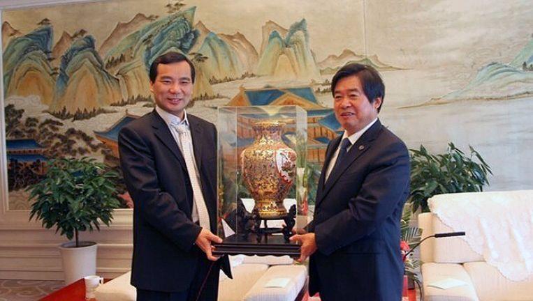 Links op de foto staat Wu Xiaohui, CEO van Anbang. Beeld