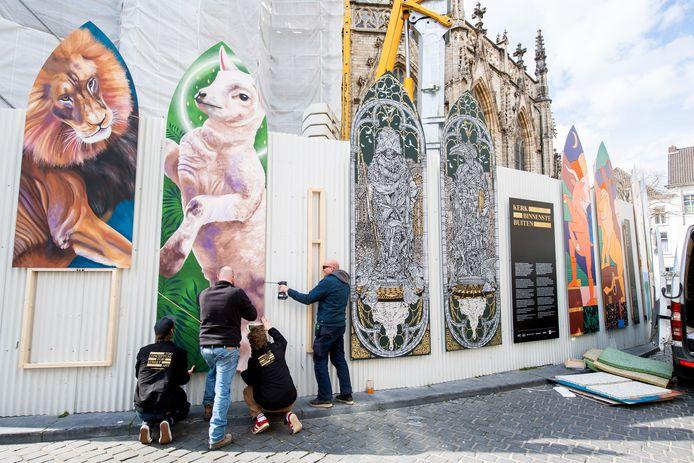 Medewerkers Blind Wall Gallery bevestigen de 'poten' onder het werk van Nina Valkhoff aan de Grote Kerk. Ernaast het nieuwe werk van MonkeyBird Crew