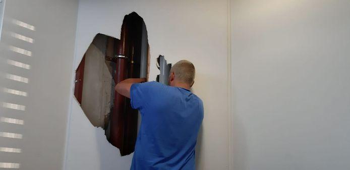 De monteur breekt voor de de spoedreparatie van de waterleiding een muur door op de vijfde verdieping.