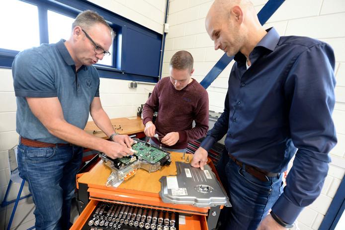 Project MBO op reis: lessen autotechniek hybride elektrische auto's voor MBO docenten bij het AST in Vriezenveen. Bij de werkbank vlnr Freek jan Dijkslag,Mark Tijhuis en trainer Leander Engelbertink.