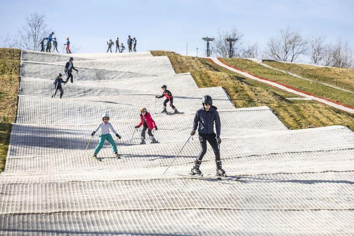 Foto van skiërs die van de borstelbaan van skicentrum Moser komen. Genomen op precies dezelfde plek als vorige week, toen er nog sneeuw lag.
