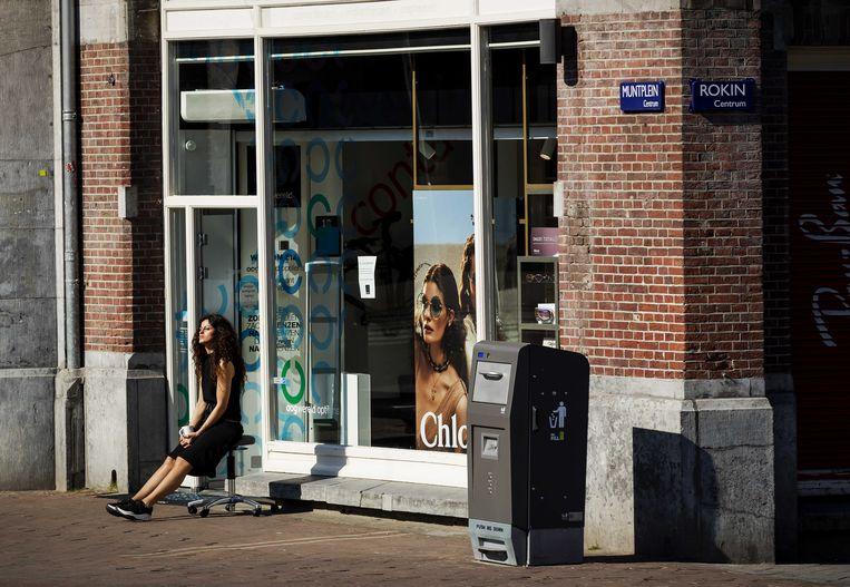 Een winkelmedewerker geniet van de zon op het Muntplein in Amsterdam.  Beeld ANP