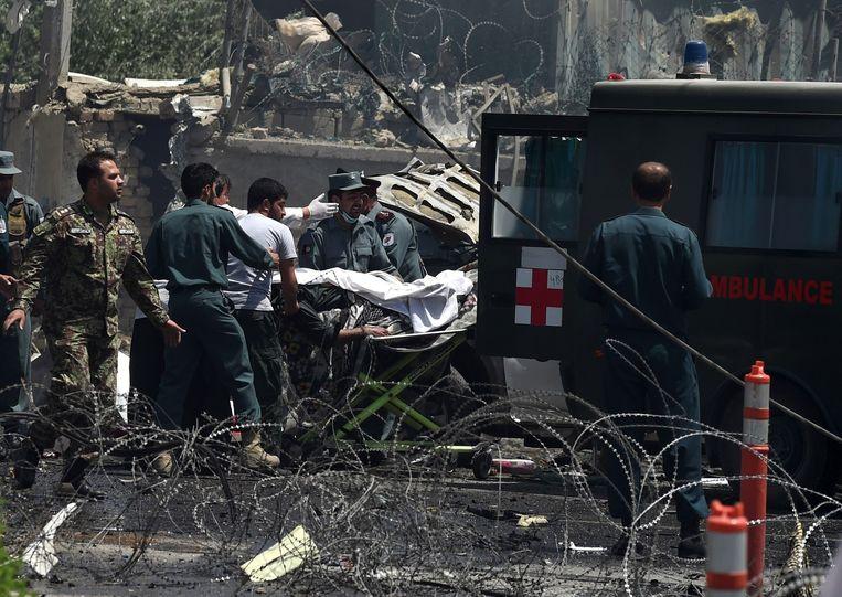 Gewonden worden afgevoerd na een grote bomexplosie in Kabul. Beeld afp
