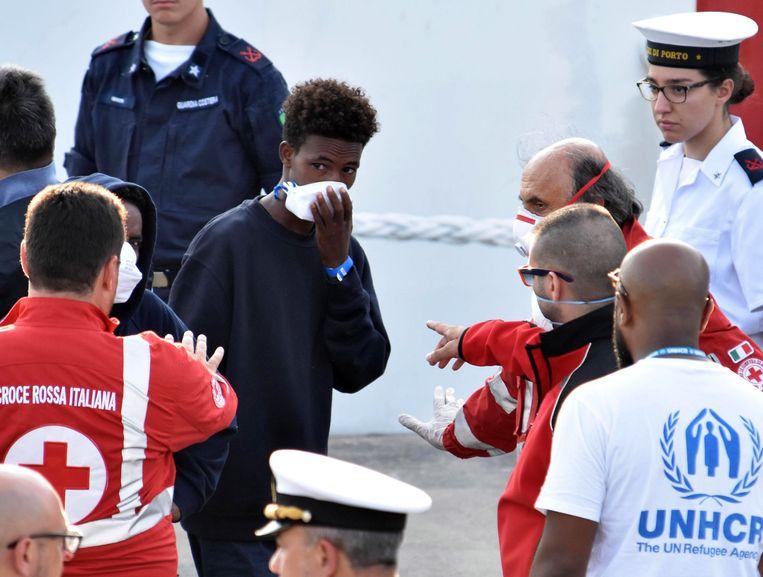 Eritrese migranten verlaten het Italiaanse marineschip Diciotti in de haven van Catania. Beeld EPA