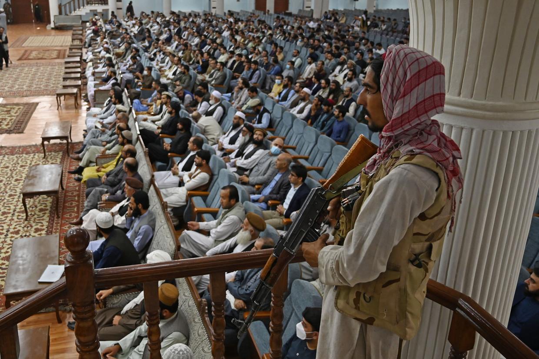 Een talibanstrijder houdt de wacht terwijl minister van Onderwijs Abdul Baqi Haqqani (niet zichtbaar) het onderwijsbeleid van de taliban uiteenzet.  Beeld AFP