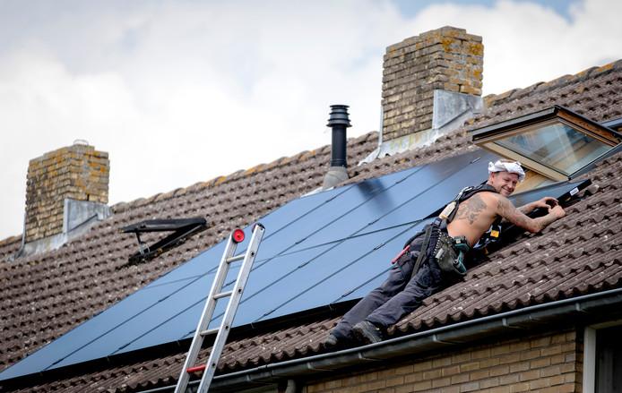Een monteur installeert zonnepanelen op het dak van een woning. De gefotografeerde is niet betrokken bij de installatie te Oost-Souburg.