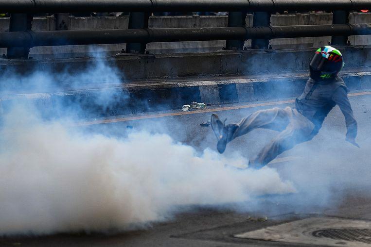 Een demonstrant in Bangkok glijdt uit terwijl hij een traangasgranaat wegschopt tijdens een betoging, gisteren, tegen de Thaise regering. De demonstranten vinden dat de regering de coronapandemie niet goed aanpakt en dat critici onterecht het zwijgen wordt opgelegd. Het aantal coronabesmettingen en sterfgevallen is in Thailand zeer hoog.  Beeld Getty Images
