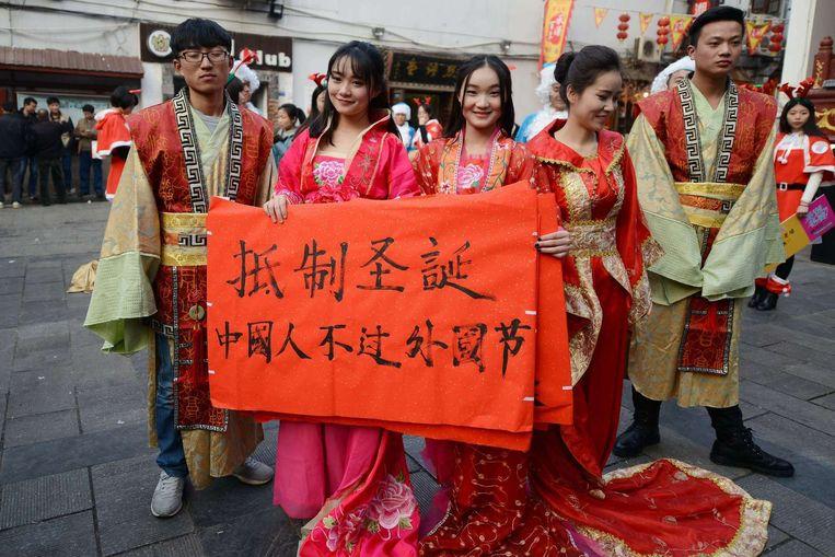 Chinese studenten in de stad Changsha protesteren tegen Kerstmis. Het spandoek luidt: 'Verzet tegen Kerstmis, Chinezen moeten geen buitenlandse feesten vieren'. Beeld afp