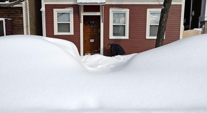 Een inwoner van Boston ruimt wel de sneeuw voor de deur.