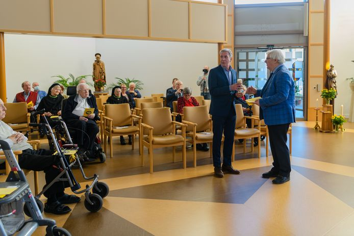Frater Wilfried van der Poll draagt de kaars over aan de nieuwe eigenaar van het klooster, vastgoedbelegger Lenferink