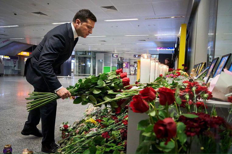 De Oekraïense president Volodimir Zelenski legt bloemen bij de luchthaven van Kiev. Beeld EPA