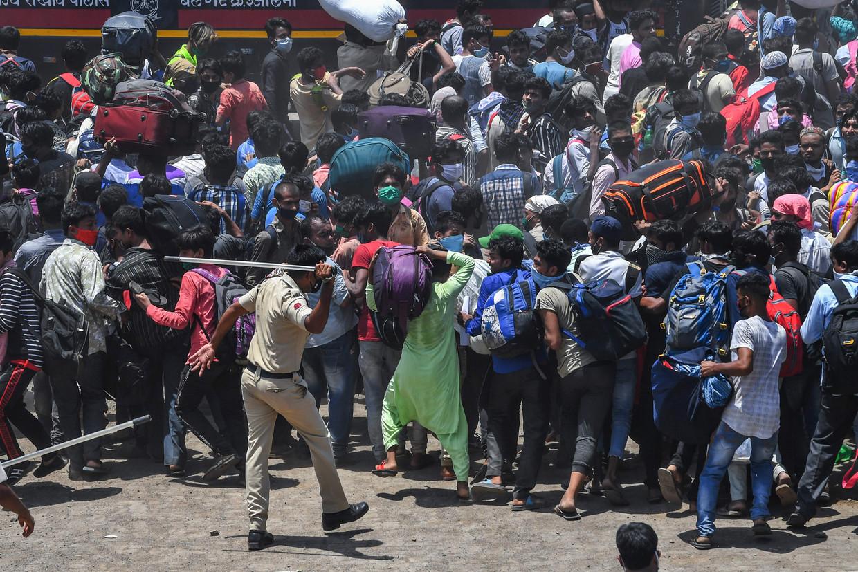 Arbeidsmigranten bij Bandra Station in Mumbai, die hopen op een trein terug naar hun geboortestreek te stappen.  Beeld AFP