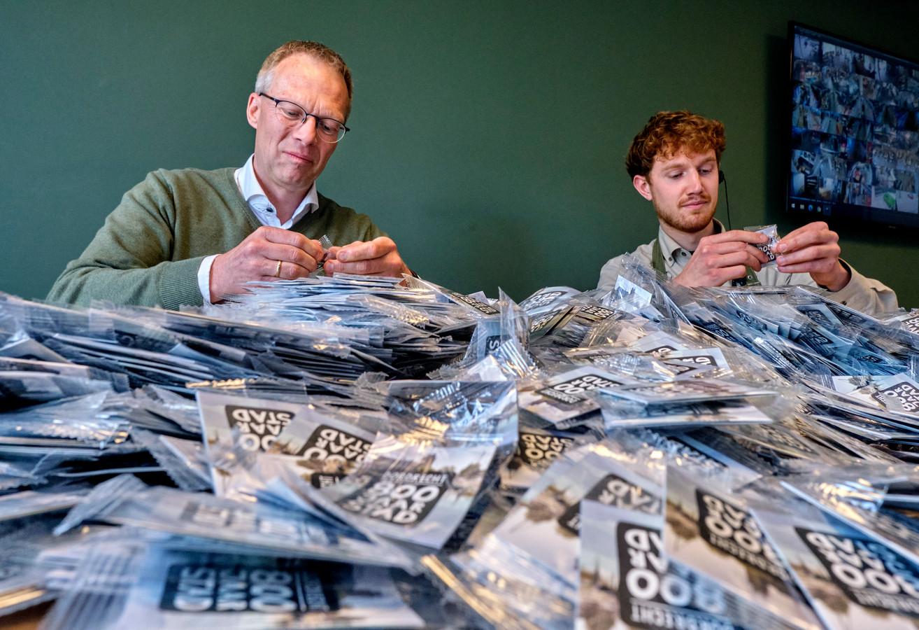 Supermarkteigenaar Pel 't Lam (links) met voor hem nog honderden plakplaatjes.