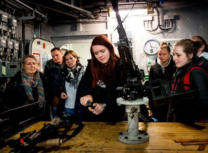 Meisjes krijgen uitleg over diverse wapens op het marineschip Zr.Ms. Tromp